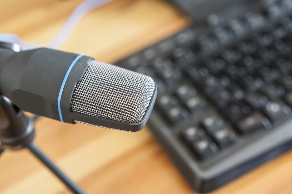 Professional microphone with computer keyboard over wooden desktop surface. Posdcast concept